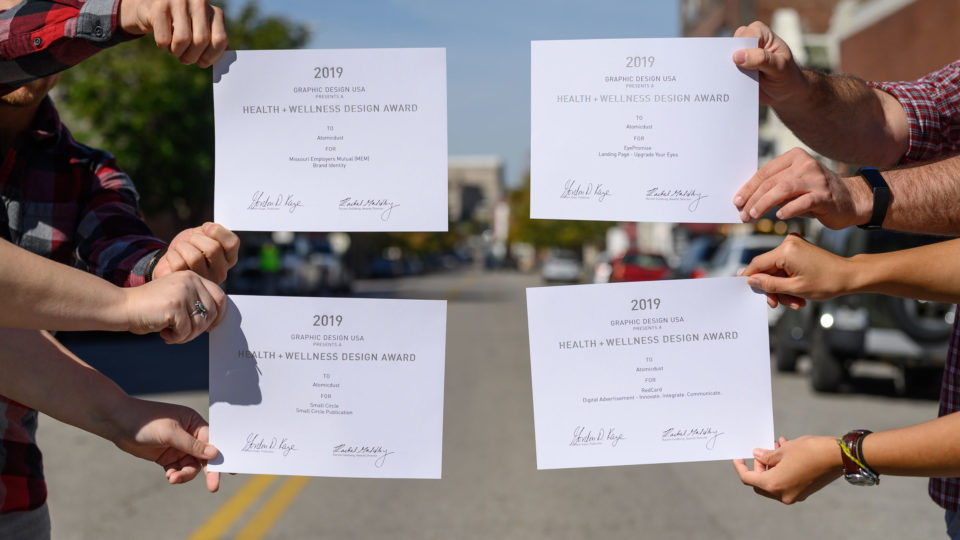 Atomicdust team members holding GDUSA Health + Wellness Design Awards certificates
