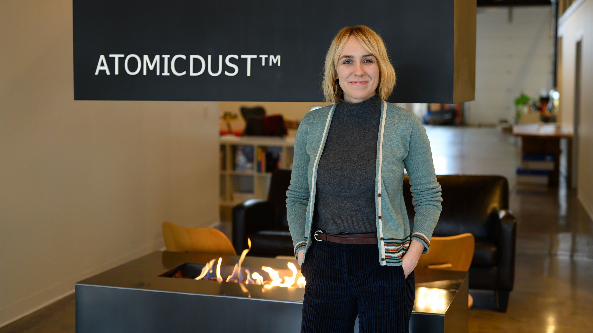 Simone stands in front of the fireplace at the Atomicdust office