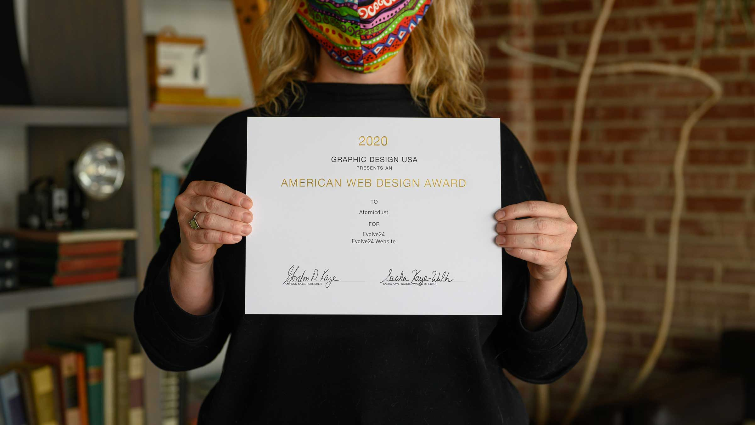 An Atomicdust team member holds a certificate from GDUSA's 2020 American Web Design Awards