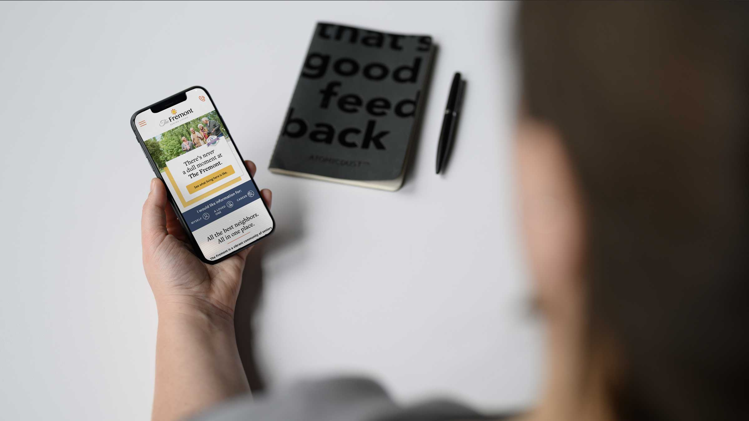 An Atomicdust team member holds an iPhone looking at the Arrow Senior Living website design